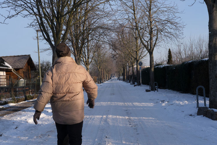 Rear view of man on snow covered field