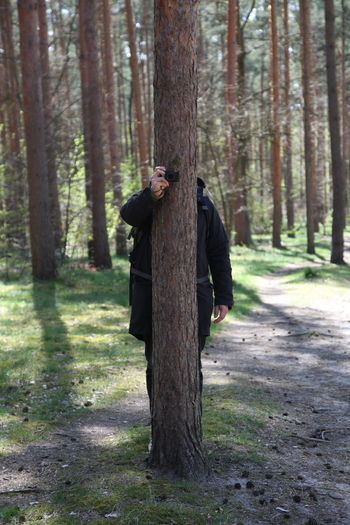 Low Section Of Man Photographing While Hiding Behind Tree In Forest
