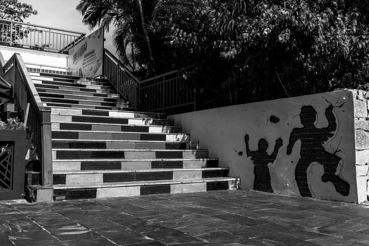 Graffiti on staircase in park against buildings in city