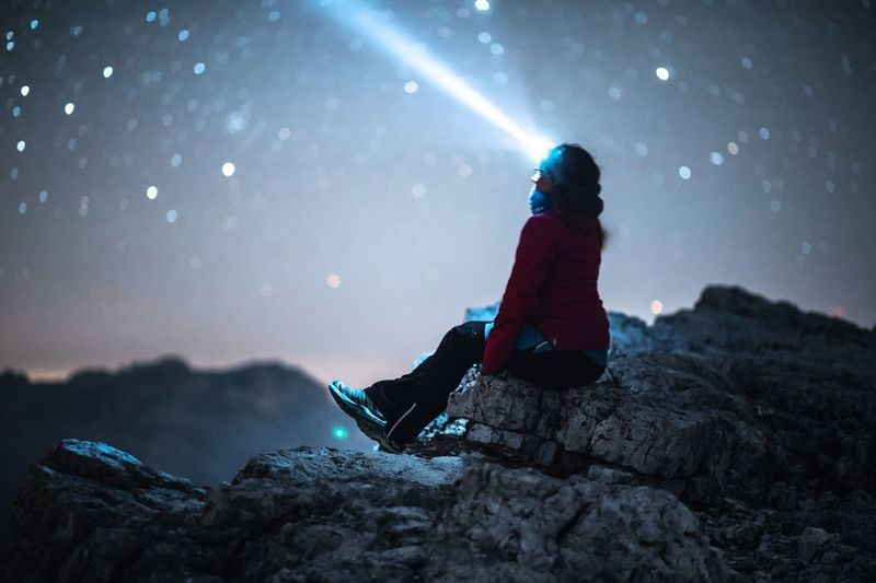 Woman Wearing Headlamp Sitting On Rock Against Sky