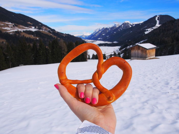 Cropped hand of woman holding pretzel over snow against sky
