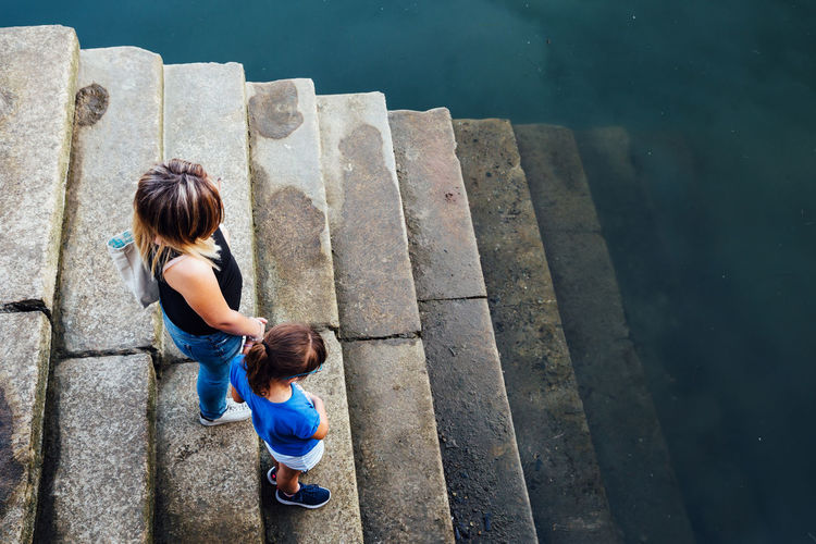 Mother and daughter on a stairway to the sea Algarve Harbor Casual Clothing Child Childhood Day Family Females Full Length Girls High Angle View Innocence Leisure Activity Lifestyles Outdoors People Real People Rear View Sea Sister Staircase Togetherness Two People Water Women