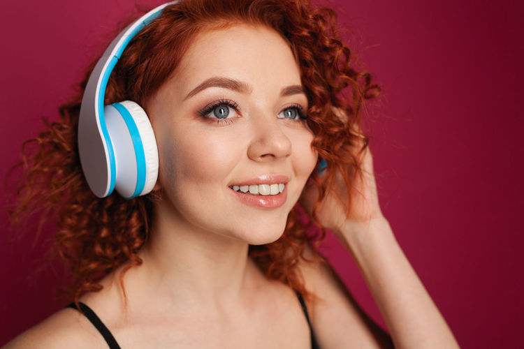 Curly redhead cute student girl Adult Beautiful People Beautiful Woman Beauty Body Part Cheerful Curly Hair Fashion Hair Hairstyle Happiness Headphones Headshot Human Body Part Human Face Indoors  Listening One Person Portrait Redhead Smiling Studio Shot Women Young Adult Young Women