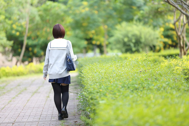 Rear view of woman in school uniform at park