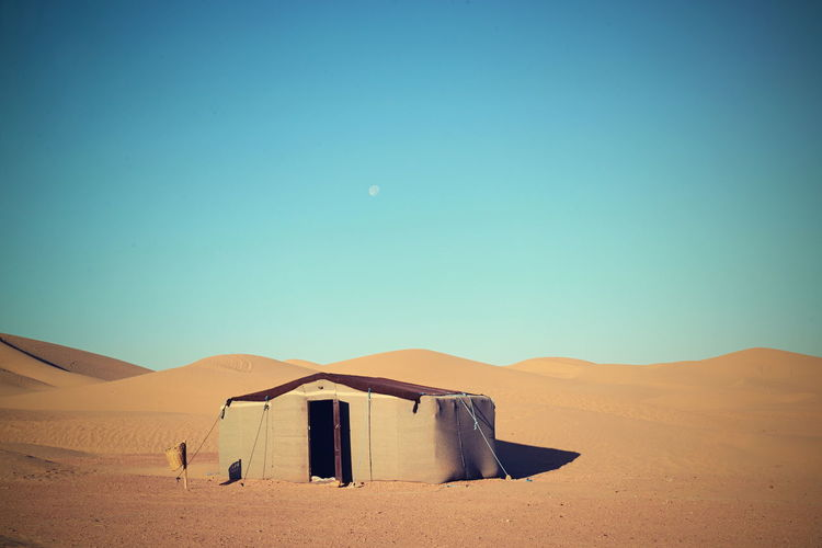 Scenic View Of Hut On Sand Dunes In Desert Against Clear Sky