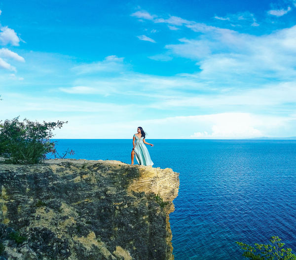 Woman standing on cliff by sea against blue sky