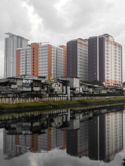 Reflection of a giant building beside a slum house Reflection Photography Reflections In The Water Reflections Reflection Reflection Perfection  Urban Skyline Urban Landscape Politics And Government Modern Low Skyscraper Water City Cityscape Business Finance And Industry Sky Building Story Infrastructure City Location Downtown District
