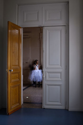 Young Woman Wearing Tutu Using Mobile Phone Seen Through Doorway
