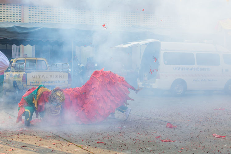 Traditional dragon dance and smoke on street