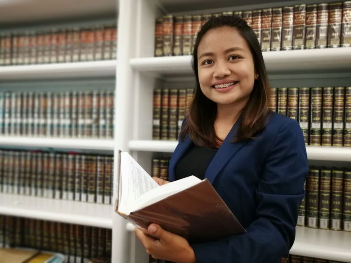 Portrait of smiling lawyer holding book in library