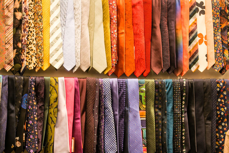 Various clothes hanging in store for sale at market stall