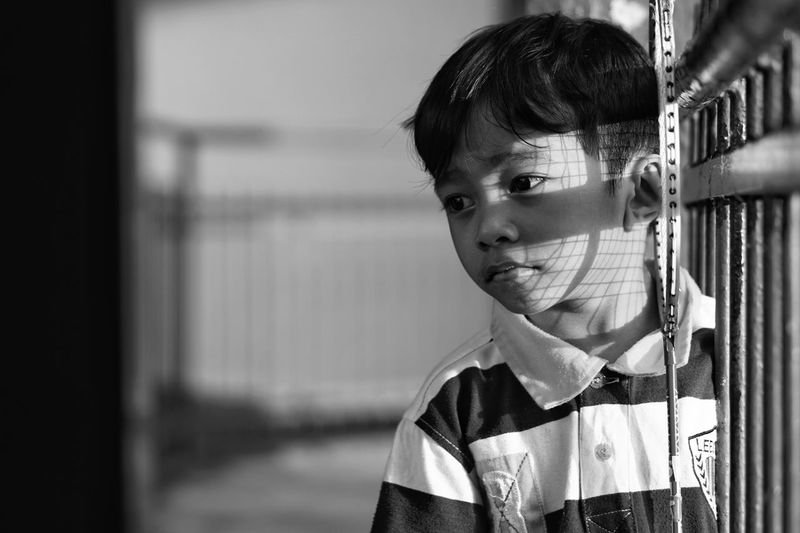 Close-up of boy looking away while standing by fence