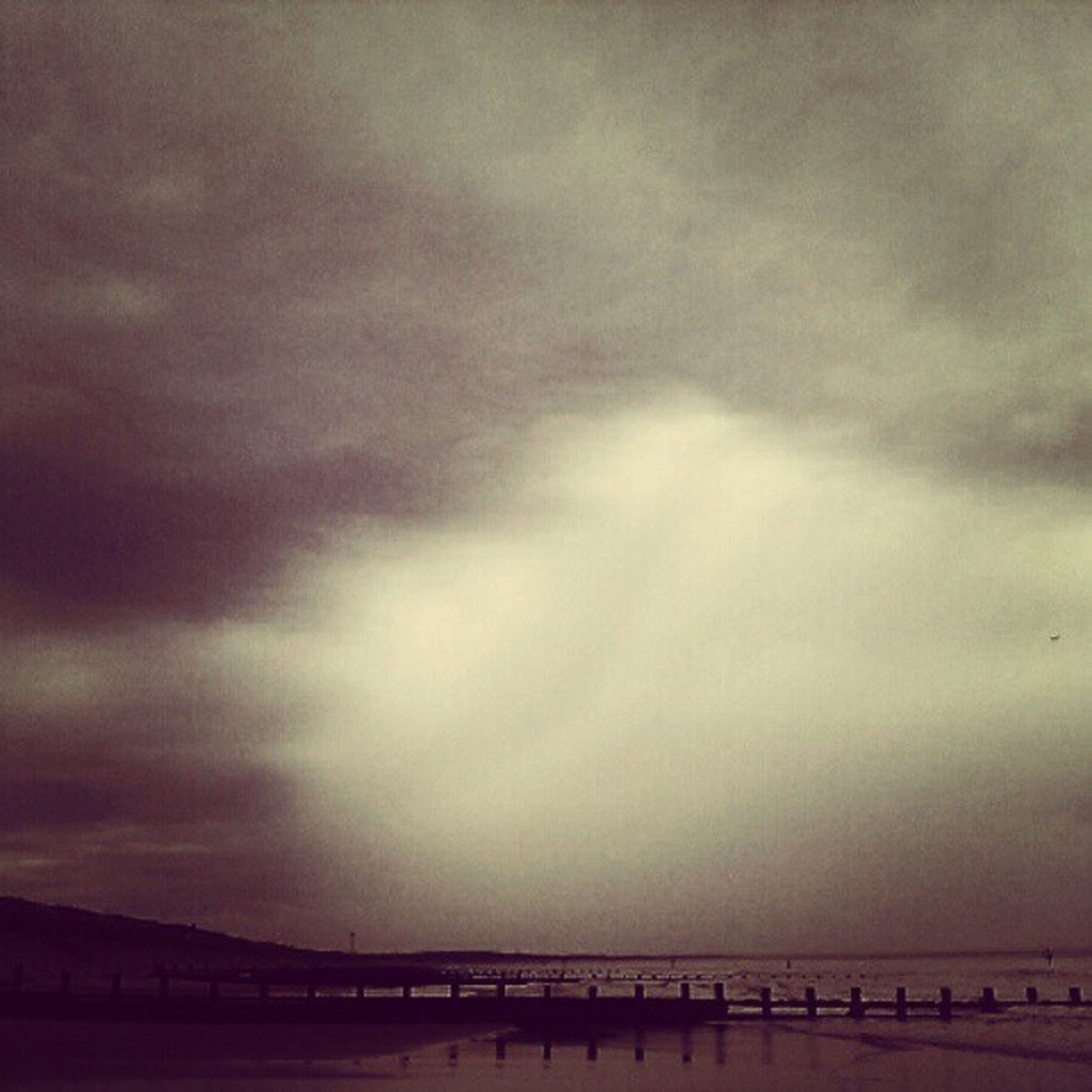 sky, sea, cloud - sky, cloudy, water, built structure, architecture, weather, scenics, nature, overcast, beauty in nature, dusk, silhouette, tranquility, tranquil scene, horizon over water, cloud, outdoors, bridge - man made structure
