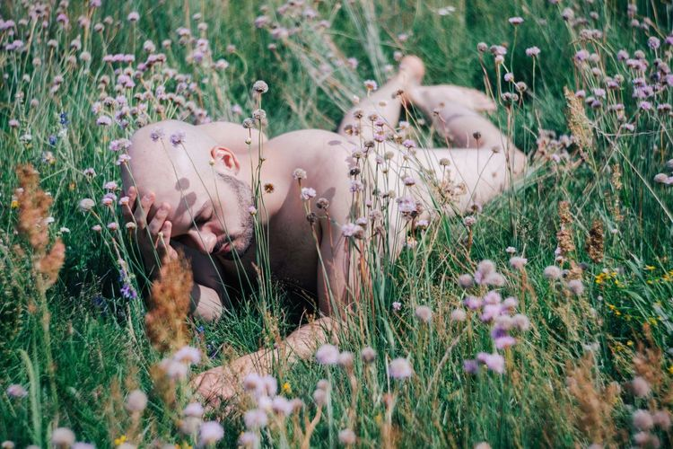 Naked man lying on field