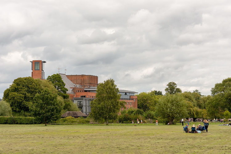 The RSC's Royal Shakespear Theatre in Stratford on Avon as viewed from across the local public park Recreation ground with a family picnicking in the foreground. Architecture Building Exterior Built Structure Cloud - Sky Day Grass Green Color Lifestyles Men Nature Outdoors People Real People Sky Togetherness Tree