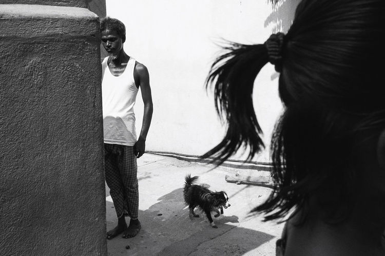 Rear view of people standing with dog