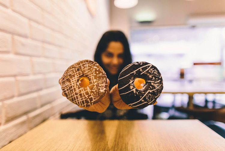 Woman Showing Donuts In Restaurant