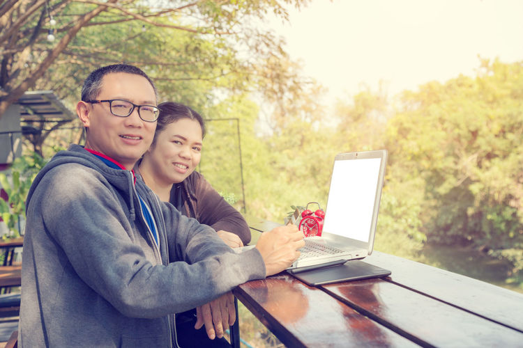 Portrait Of Smiling Man And Woman Using Laptop Outdoors