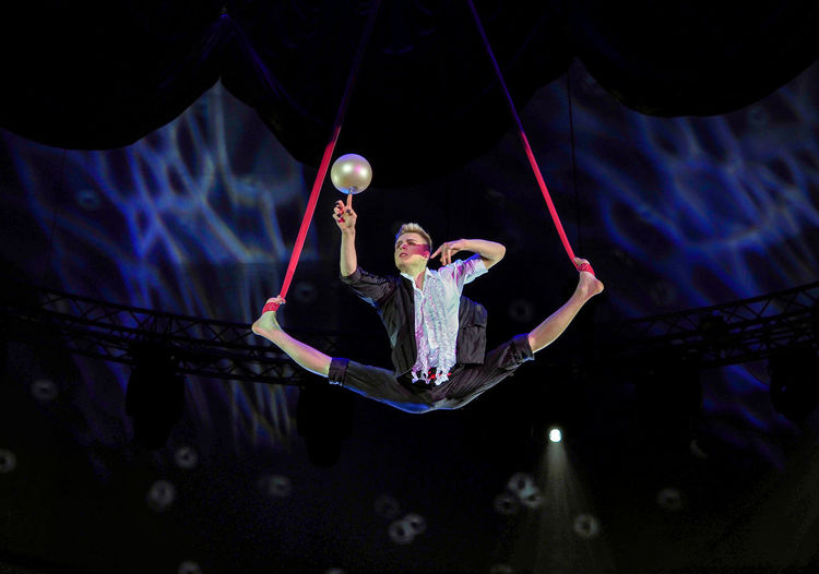 Russia, Moscow. the Nikulin circus, trapeze Adult Adults Only Arts Culture And Entertainment Challenge Circus Human Body Part Moscow Motion Night One Man Only One Person Outdoors People Performance Performing Arts Event Russia Russian Circus Sportsman The Nikulin Circus Trapeze Trapeze Artist Young Adult