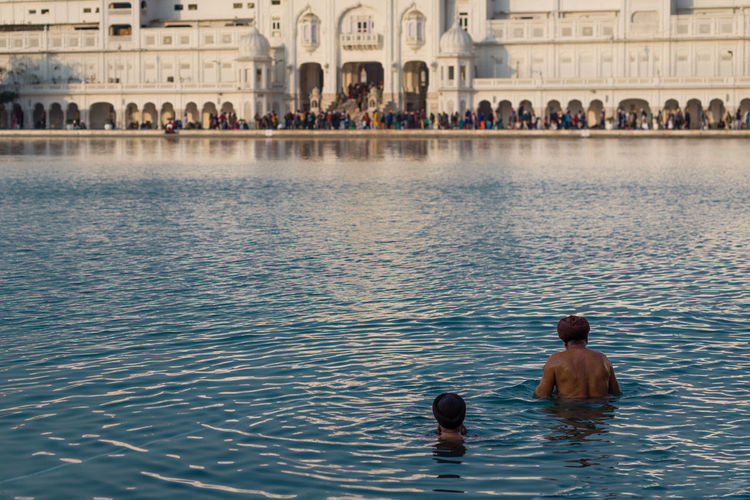 Two male sikh men inside the Holy Pool of Immortal Nectar in the Golden Temple of Amritsar, India Amritsar Cleaning Copy Space Famous Place Golden Golden Temple Harmandir Sahib Holy Immortal India Indian Nectar Pool Punjab Punjabi Religion Sikh Sikh Temple Sikhism Temple Turban Washing Water Worship