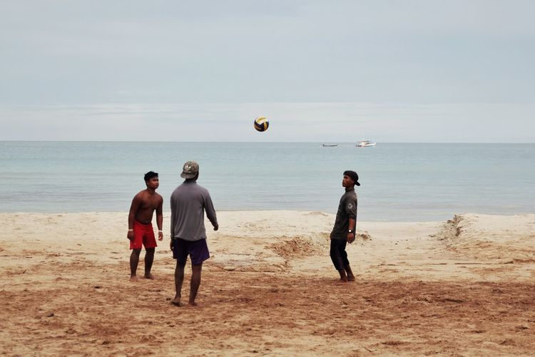 Rear view of men playing with ball on beach