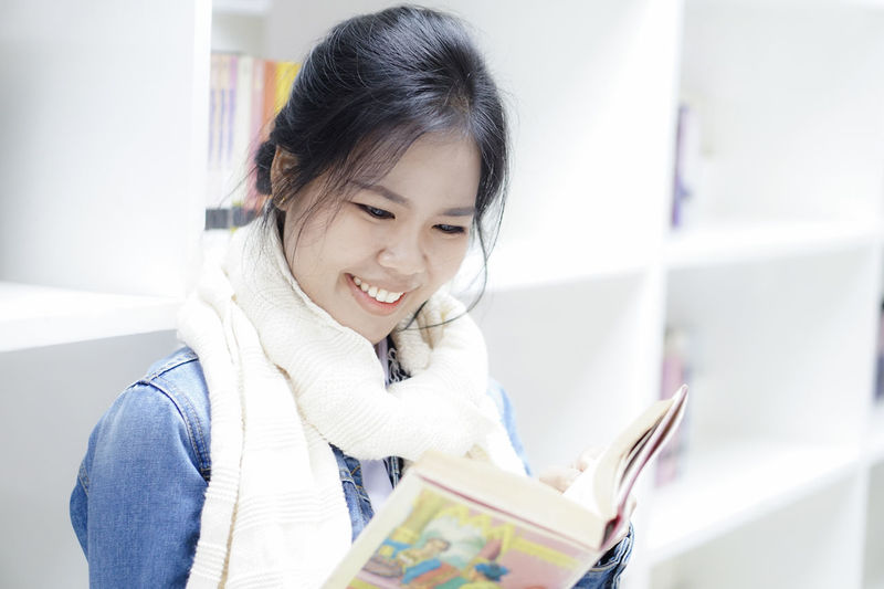 Young woman reading book at library