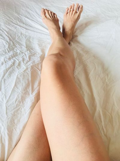 Low section of woman on bed at home