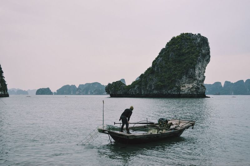 Man Standing On Boat In Halong Bay With Rocky Mountains In Background Against Clear Sky