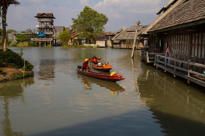 People sailing boats on canal by stilt houses