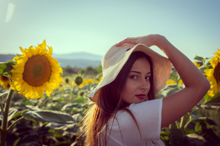 Portrait of beautiful young woman with yellow flowers against sky