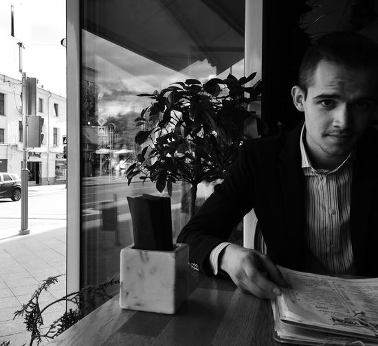 Man sitting with menu at table in restaurant