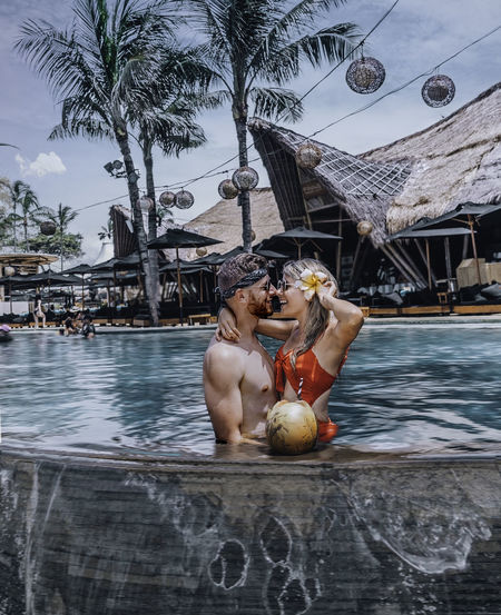 Smiling couple embracing while standing in swimming pool