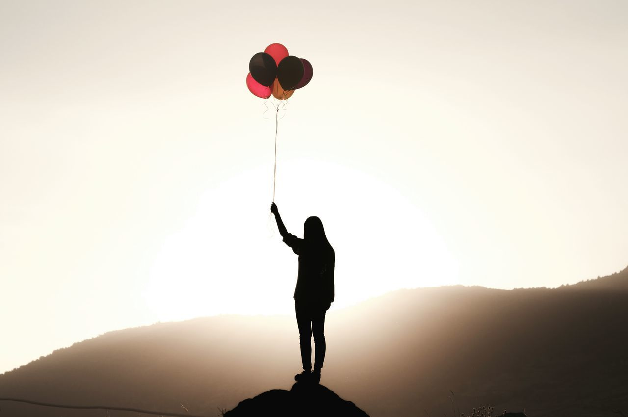 Full Length Of Silhouette Woman Holding Colorful Balloons On Cliff Against Mountain