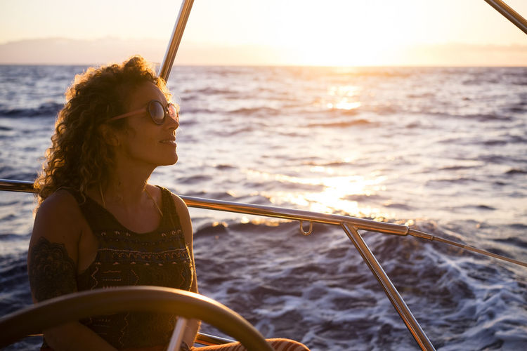 Woman sitting on boat in sea against sky