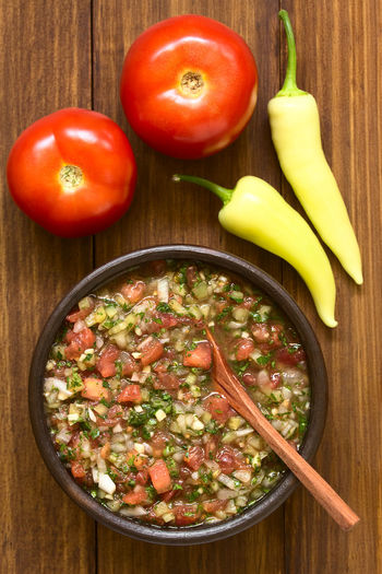 Chilean Pebre sauce, a traditional condiment made of tomato, onion, garlic, spicy aji pepper and coriander, photographed overhead on dark wood with natural light (Selective Focus, Focus on the top of the pebre and the tomatoes) Aji Chile Chilean  Garlic Salad Spicy Vegetarian Accompaniment Chilean Food Chili  Cilantro Condiment Coriander Food Food And Drink Onion Pebre Pepper Salsa Sauce Spread Tomato Vegan Vegetable Vegetarian Food