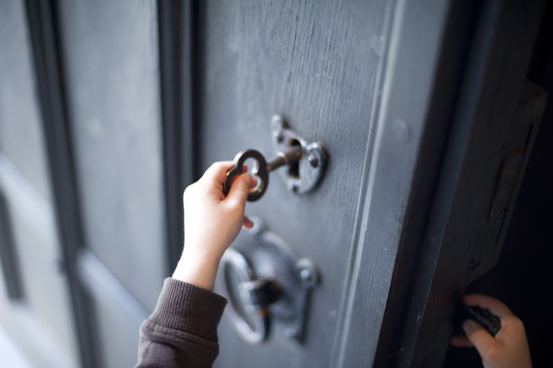 Cropped view image of the hands of a child unlocking a wooden door with a large old-fashioned brass key Adventure Child Close-up Detail Door Doorway Exploring Hands Home House Inquisitive Key Lock Old-fashioned Opening Opportunity Possibilities  Retro Safety Security Unlocking Wood
