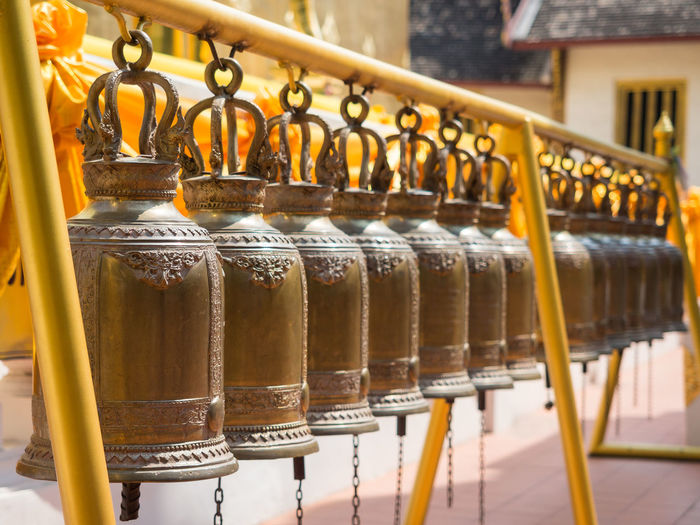 Close-up of metal bells in a row at buddhist temple wat phra singh, chiang mai, thailand