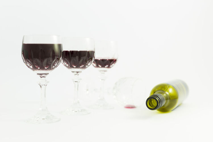 Concept of alcohol consumption, alcoholism and abuse with a line of beautiful crystal glasses filled with red wine, a full and an empty bottle. Stages of drinking underlined by blurred image effect. Drunken Elegant Green Color Objects Red Wine Wine Bottle Abuse Alcohol Alcoholic  Alcoholic Drink Background Blurred Background Close-up Drinking Drinking Glass Empty Group Of Objects Leisure Activity No People Red Wine Still Life Studio Shot White Color Wine Wineglass