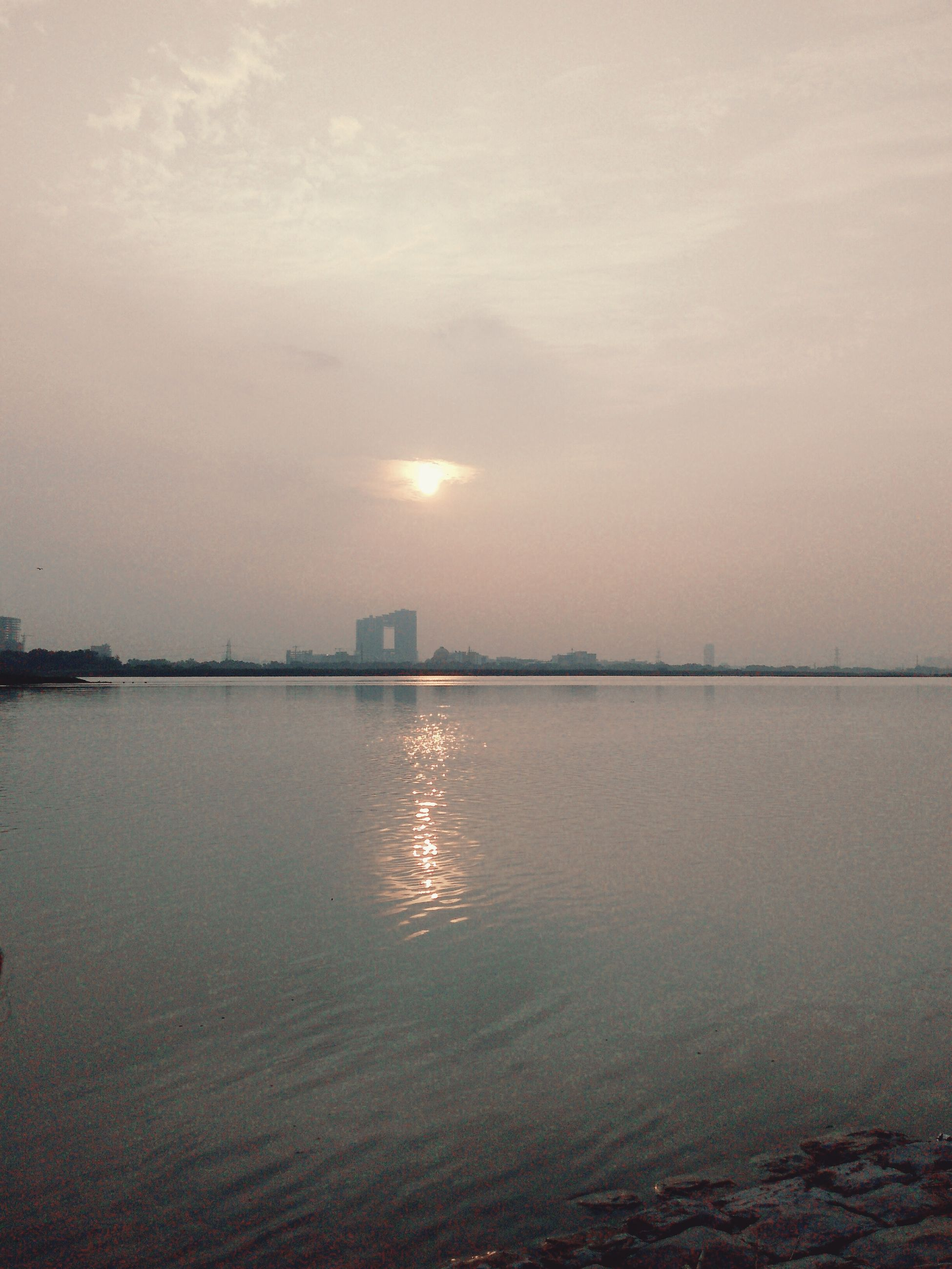 water, sunset, scenics, tranquil scene, sun, tranquility, reflection, sea, beauty in nature, sky, idyllic, seascape, nature, waterfront, cloud, calm, majestic, remote, distant, atmosphere, outdoors, non-urban scene, vacations, no people, urban skyline, ocean, cloud - sky, lens flare, atmospheric mood, moody sky, dramatic sky