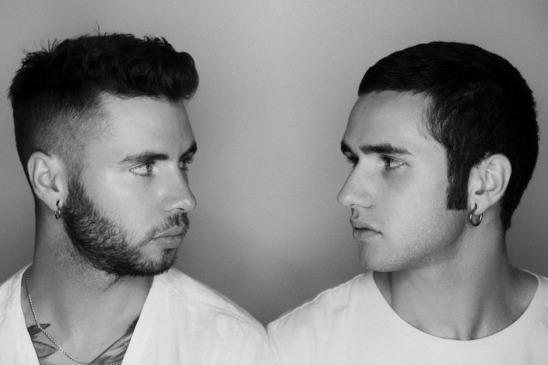 Close-Up Of Gay Couple Looking At Each Other While Standing Against Wall