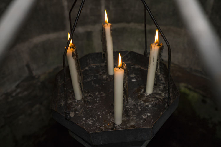 Close-up of lit candles in temple against building