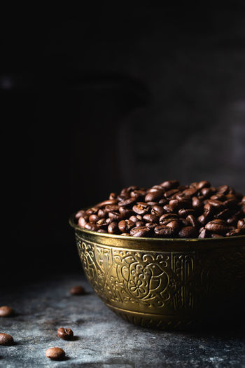 Close-up of coffee beans on table against black background