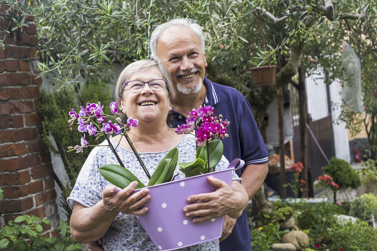 Cheerful Couple With Flowers In Basket At Yard