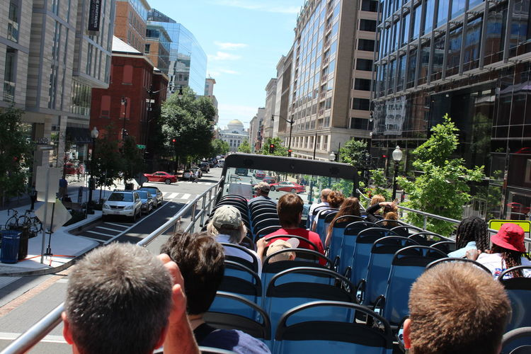 Rear View Of People Sitting On Tour Bus In City