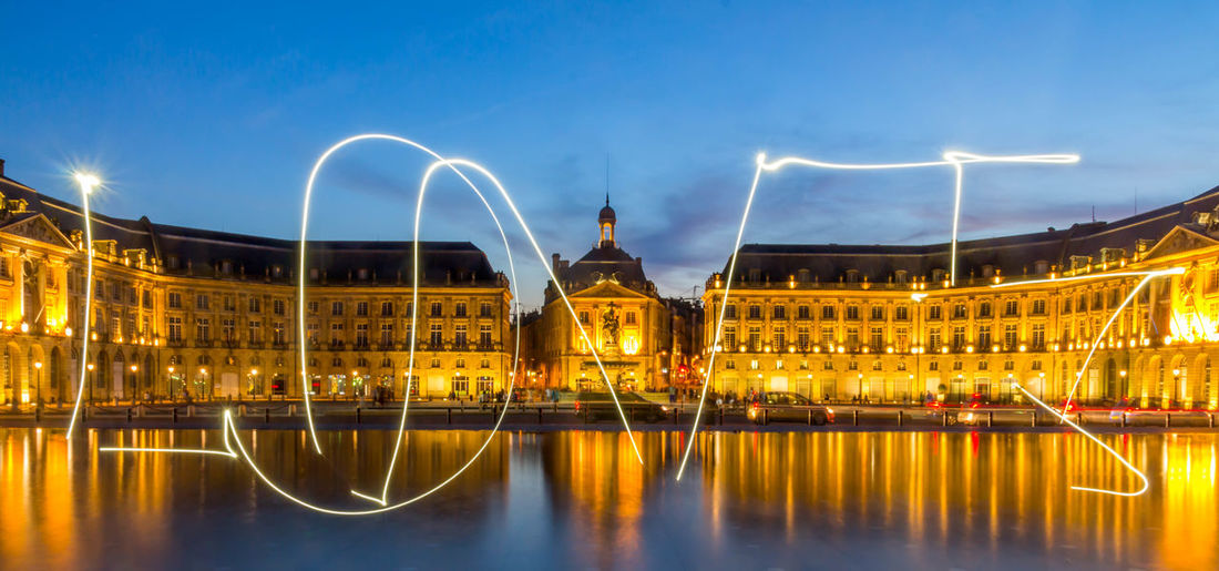 Illuminated Building Reflecting In Lake With Light Trail Word Love In Foreground