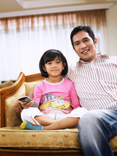 Father And Daughter Watching Tv Sitting On Sofa At Home
