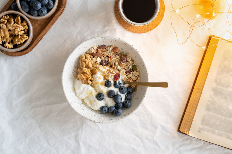 Top view book and christmas healthy lifestyle breakfast with granola muesli and yogurt in bowl