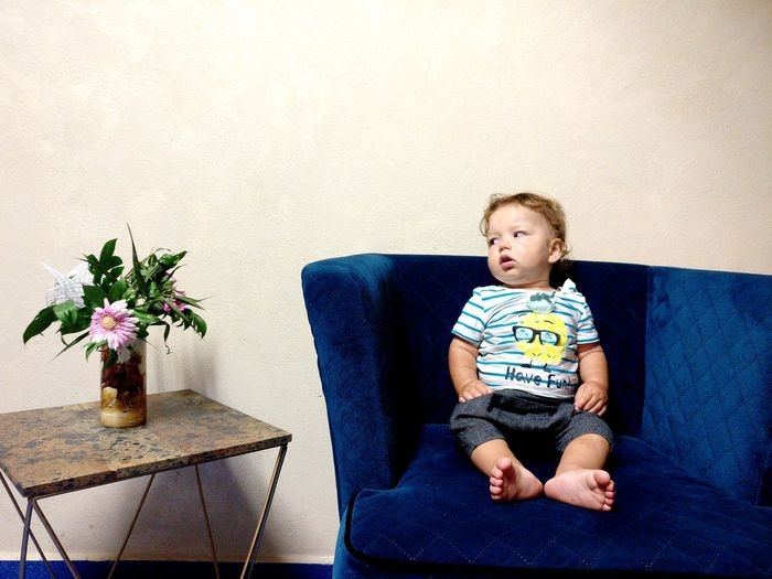 Full length of cute baby boy sitting on chair against wall at home