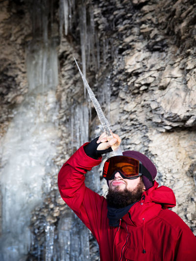 One Person Adult Holding Clothing Men Nature Activity Leisure Activity Waterfall Day Water Motion Young Adult Facial Hair Mid Adult Sunglasses Outdoors Warm Clothing Winter Unicorn Ice Icicle Fun Bearded Rock - Object