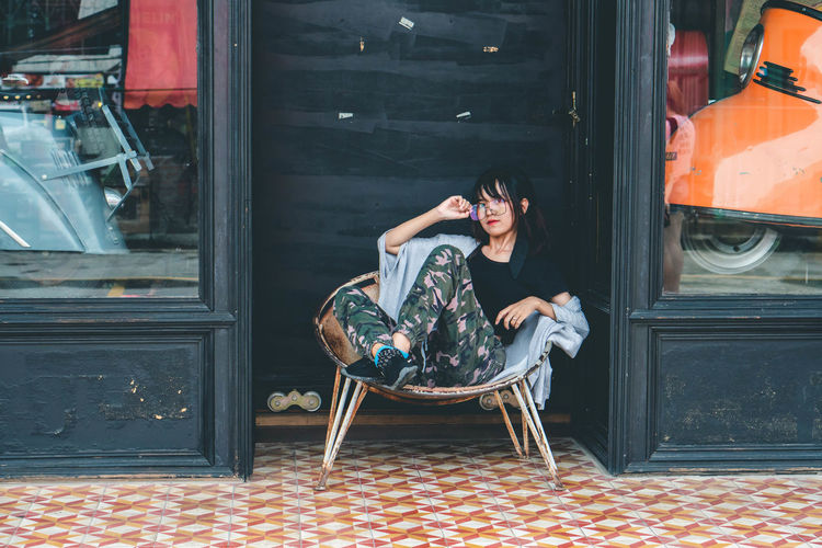 Portrait Of Woman Sitting On Chair Outside Store